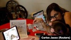 Isabel Martin del Campo, membantu putrinya Ines, 6 tahun, di kelas bahasa Inggrisnya. Jutaan siswa kembali ke kelas secara virtual setelah sekolah ditutup sejak Maret karena wabah Covid-19, Mexico City, Meksiko, 24 Agustus 2020. (Foto: REUTERS/Carlos Jass