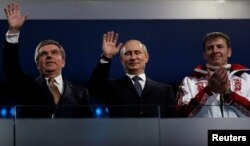 FILE - International Olympic Committee (IOC) President Thomas Bach of Germany and Russian President Vladimir Putin wave as gold medalist bobsleigh athlete Russia's Alexander Zubkov applauds during the closing ceremony for the 2014 Sochi Winter Olympics, Feb. 23, 2014.