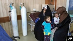 In this Friday, March 11, 2016 photo, people exposed to a chemical attack wait for treatment at a hospital in Taza, 10 miles (20 kilometers) south of Kirkuk in northern Iraq.