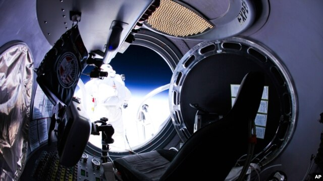 This photo provided by Red Bull Stratos shows pilot Felix Baumgartner of Austria as he jumps out of the capsule, October 14, 2012.