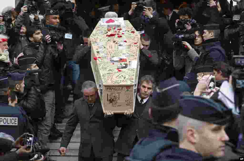 Pallbearers carry the casket of Charlie Hebdo cartoonist Bernard Verlhac, known as Tignous, decorated by friends and colleagues of the French satirical weekly, at the city hall of Montreuil, outside of Paris. Funerals are being held for last six staff members of the satirical weekly, who were killed last week in a terror attack at their office in Paris.