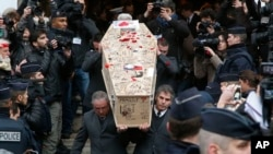 Pallbearers carry the casket of Charlie Hebdo cartoonist Bernard Verlhac, known as Tignous, decorated by friends and colleagues of the satirical newspaper Charlie Hebdo, at Montreuil city hall east of Paris, Jan. 15, 2015.