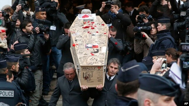 Pallbearers carry the decorated casket of Charlie Hebdo cartoonist Bernard Verlhac, known as Tignous, at the city hall of Montreuil, east of Paris, Jan. 15, 2015. A new report details jihadist threats against journalists.