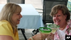 This May 31, 2013 photo shows baby boomers Benita Munger, left, and Judy Palladino toasting during a game night gathering in Mayfield Village, Ohio.