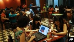 Three young Vietnamese girls use a laptop and smart phones to go online at a cafe in Ha Noi, Viet Nam Wednesday, May 14, 2013. (AP Photo/Na Son Nguyen).