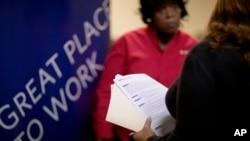 Seorang pelamar pekerjaan bercakap-cakap dengan seorang perekrut di sebuah bursa tenaga kerja di Marietta, negara bagian Georgia.