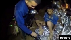 Boys from the under-16 soccer team trapped inside Tham Luang cave receive treatment from a medic in Chiang Rai, Thailand, in this still image taken from a July 3, 2018 video by Thai Navy Seal.