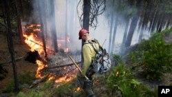 미국 캘리포니아주 요세미티 국립공원 주변에서 대형 산불이 열흘째 계속되는 가운데, 27일 소방관이 산불을 진화하고 있다.