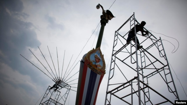 "Workers prepare lighting and sound stands for a rally by pro-government ""red shirt"" supporters in Nakorn Pathorn province, west of Bangkok, April 4, 2014."
