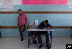 In this Sunday, May 26, 2019 photo, a teacher supervises while two Palestinian school children attend a final exam at the United Nations Relief and Works Agency for Palestine Refugees in the Near East, UNRWA, Hebron Boys School.