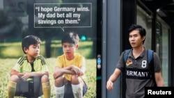 Seorang pria melewati iklan layanan masyarakat anti-judi bertema Piala Dunia di tempat menunggu taksi di Singapura (9/7). (Reuters/Edgar Su)