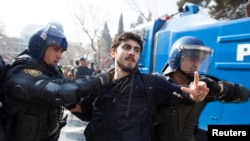 Riot police detain a protester during a rally in Baku, March 10, 2013.