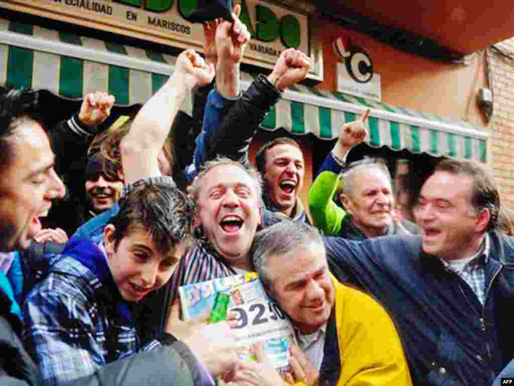 """People celebrate after winning a portion of the main prize of Spain's Christmas lottery in Palleja, Spain, Wednesday, Dec. 22, 2010. Spain's beloved Christmas lottery known as """"El Gordo"""" (The Fat One) spread euro2.3 billion ($3 billion) in holiday cheer W"""
