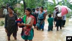 Cư dân Nepal vác đồ đạc lội qua con đường bị ngập lụt ở Bardia, phía tây Nepal, ngày 15/8/2014.