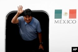 Former Bolivian President Evo Morales waves upon arrival to Mexico City, , Nov. 12, 2019. Mexico granted asylum to Morales, who resigned on Nov. 10 under mounting pressure from the military and the public.
