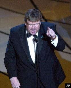 "FILE - Michael Moore makes a statement after accepting the Oscar for best documentary feature for the film ""Bowling for Columbine"" during the 75th annual Academy Awards, March 23, 2003, in Los Angeles."