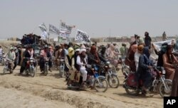 Supporters of the Taliban carry Islamic flags after the Taliban said they seized the Afghan border town of Spin Boldaka across from the town of Chaman, Pakistan, July 14, 2021.