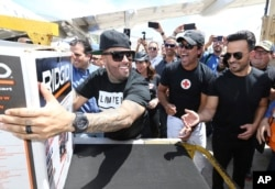 Singers Nicky Jam, Chayanne and Luis Fonsi unload supplies from a JetBlue aircraft at Luis Muñoz Marín International Airport in San Juan, Puerto Rico.
