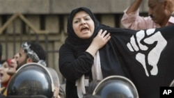 A protester in Egypt, behind a cordon of security officers, calls for an end to police brutality, Cairo, 13 Apr 2010
