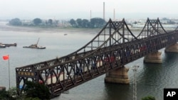 FILE - Trucks cross the friendship bridge connecting China and North Korea in the Chinese border town of Dandong, opposite side of the North Korean town of Sinuiju, Sept. 4, 2017. For Chinese traders, United Nations sanctions on North Korea are a disaster. Business in the Chinese border city of Dandong has all but dried up.