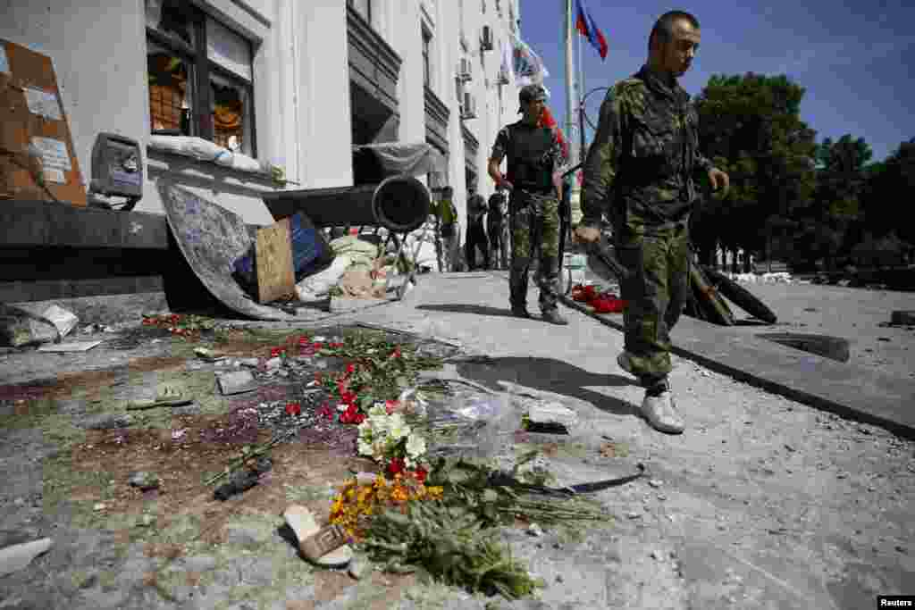 An armed pro-Russian separatist walks near the site of an explosion in a regional administration building in the eastern Ukrainian city of Luhansk June 3, 2014.
