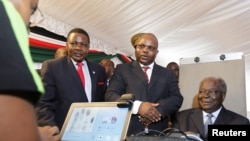 Kenyan President Mwai Kibaki (R) registers as a voter before launching the nationwide, one-month biometric voter registration (BVR) exercise in the capital Nairobi, November 19, 2012.