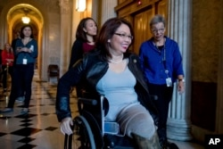 FILE - Sen. Tammy Duckworth, D-Ill. arrives for a closed-door Democratic policy luncheon on Capitol Hill in Washington.