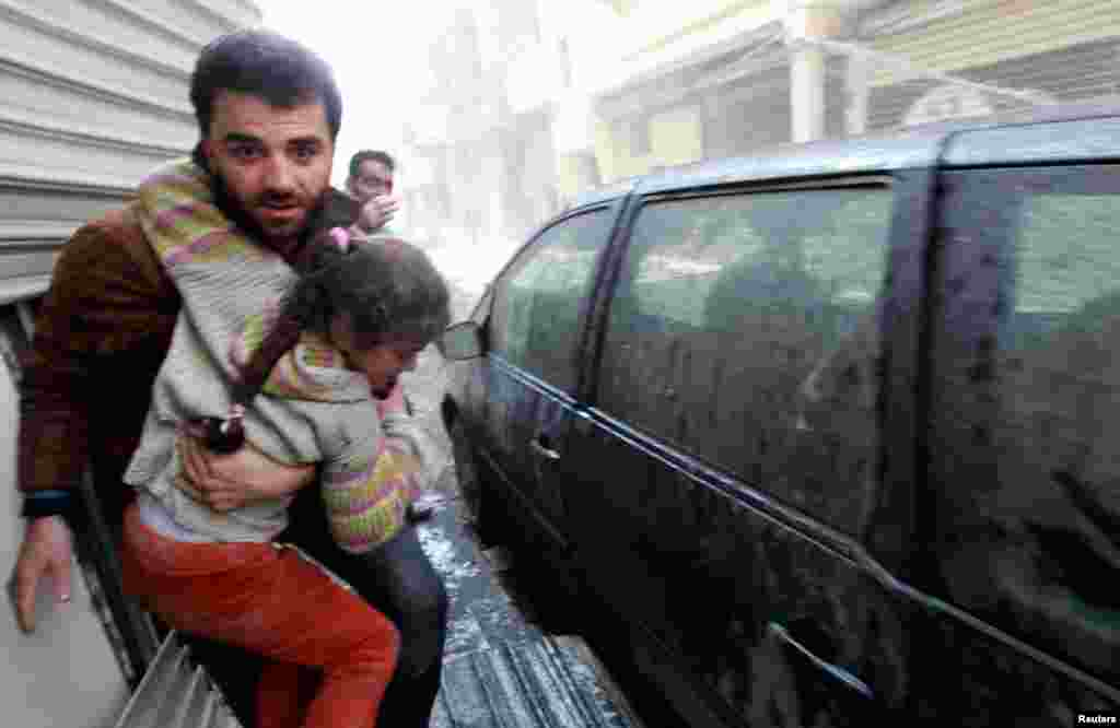 Civilians run to take cover after a jet missile hit the al-Myassar neighborhood of Aleppo, February 20, 2013.