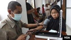 Petugas kesehatan memeriksa tekanan darah seorang pasien lanjut usia di sebuah Puskesmas di Jakarta. (Foto: dok).