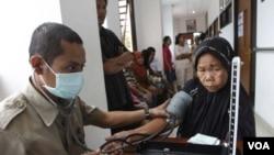 Petugas kesehatan memeriksa tekanan darah seorang pasien lanjut usia di sebuah Puskesmas di Jakarta. (Foto: Dok)
