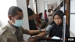 Petugas kesehatan memeriksa tekanan darah seorang pasien lanjut usia di sebuah Puskesmas di Jakarta. Populasi manula di Indonesia diperkirakan akan meningkat empat kali lipat 12 tahun dari sekarang.