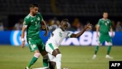 Riyad Mahrez, à gauche, en lutte avec Sadio Mane lors du match de poule de la CAN 2019 entre le Sénégal et l'Algérie, Caire, le 27 juin 2019