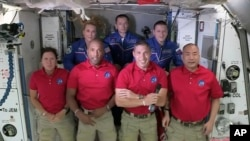 In this frame grab from NASA TV, SpaceX Dragon crew, from front left to right, Shannon Walker, Victor Glover, Mike Hopkins and Soichi Noguchi stand with International Space Station crew Kate Rubins, from back left, Expedition 64 commander Sergey Ryzhikov
