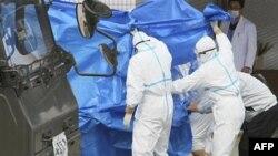 Thành viên Lực lượng Phòng vệ Nhật trong trang phục bảo hộ giúp đưa các công nhân bị nhiễm phóng xạ ra ngoài