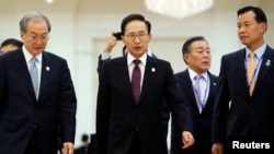 South Korean President Lee Myung-bak (C) is followed by his staff as he leaves the Plenary session of the 21st ASEAN (Association of Southeast Asian Nations) and East Asia summits in Phnom Penh November 20, 2012