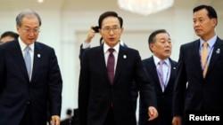 ໃນເວລານັ້ນ ປະທານາທິບໍດີ ເກົາຫຼີໃຕ້ ທ່ານ ລີ ມີຢຸງ-ບັກ (Lee Myung-bak) (ກາງ) ຕິດຕາມມາດ້ວຍ ຄະນະຂອງທ່ານ ໃນຂະນະທີ່ຍ່າງອອກມາຈາກ ກອງປະຊຸມສຸດຍອດ ສະໄໝສາມັນ ຄັ້ງທີ 21 ຂອງອາຊຽນ (ASEAN Association of Southeast Asian Nations) ແລະເອເຊຍ ຕາເວັນອອກ ໃນນະຄອນຫຼວງ ພະນົມ ເປັນ, ວັນທີ 20 ພະຈິກ 2012.