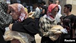 Warga provinsi Idlib di Suriah membeli roti di satu-satunya toko roti yang buka (foto: Reuters/Zohra Bensemra).