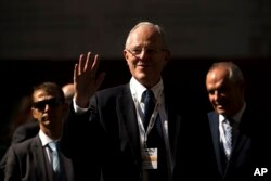 FILE - Peru's President Pedro Pablo Kuczynski waves as he arrives to an economic forum about Peru after his meeting with Spain's Prime Minister Mariano Rajoy in Madrid, Spain, June 12, 2017.