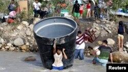 Người Columbia mang vác vật dụng băng qua sông Tachira để vào lại Colombia sau khi bị trục xuất khỏi Venezuela hôm 25/8/2015.