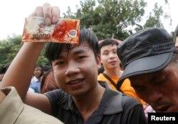 Sau khi lợn bị chém chết, những người tham dự đua nhau lấy tiền quết vào các vũng máu tung tóe để 'lấy lộc, cầu may.'