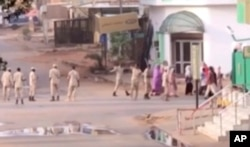 In this image made from video, Sudanese forces escort civilian in Khartoum, Sudan on June 3, 2019.