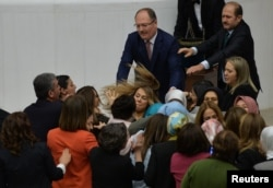 Ruling AK Party and opposition lawmakers scuffle after the independent lawmaker Aylin Nazliaka (not pictured) handcuffed herself to the rostrum during a debate to protest against the proposed constitutional changes at the Turkish Parliament in Ankara, Turkey.