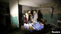 Phụ huynh và học sinh nấp trong tầng hầm của một ngôi trường được dùng là hầm trú ẩn trong khi pháo kích xảy ra ở Donetsk, 1/10/14