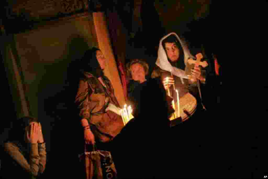 Christian worshippers pray in the Golgotha, or Calvary, inside the Church of the Holy Sepulchre, traditionally believed to be the burial site of Jesus Christ, in Jerusalem's Old City, Wednesday, April 11, 2012. (AP Photo/Bernat Armangue)