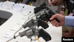 A man holds a gun in the exhibit hall of the George R. Brown Convention Center, the site for the National Rifle Association's (NRA) annual meeting in Houston, Texas, May 3, 2013.
