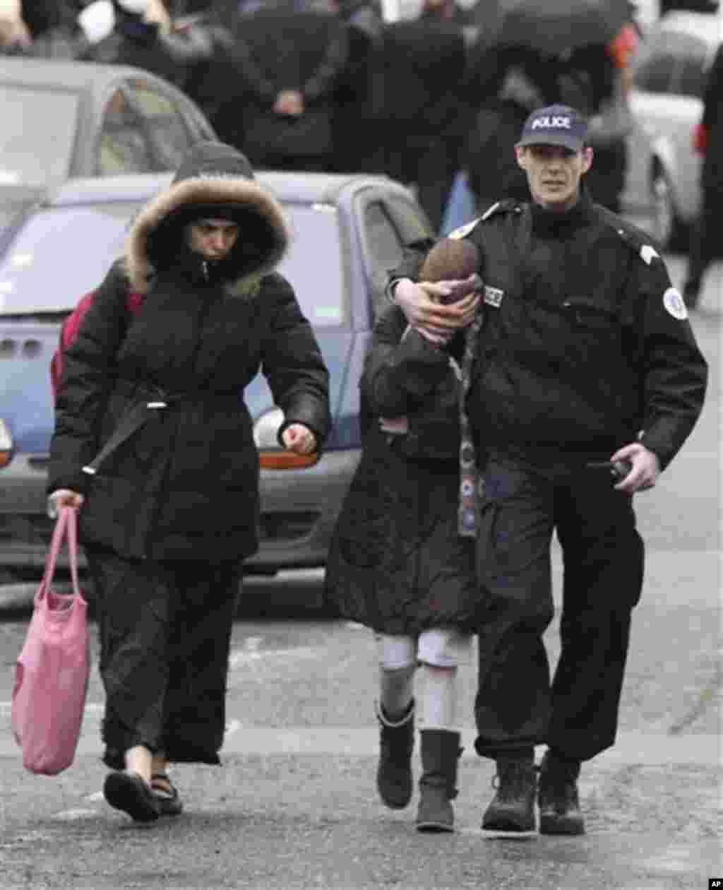 A student, center, flanked by an unidentified woman and a police officer leave a Jewish school where a gunman opened fire killing four people in Toulouse, southwestern France, Monday, March 19, 2012. A father and his two sons were among four people who di