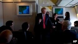 El Presidente Donald Trump habla con los periodistas a bordo del Air Force One, mientras viaja al Aeropuerto Internacional de Palm Beach en West Palm Beach, Florida.