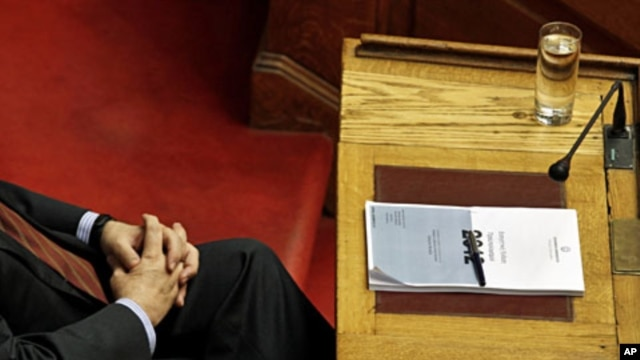 Greek PM Lucas Papademos attends a parliament session with a copy of Greece's 2012 budget placed on his desk in Athens, November 18, 2011
