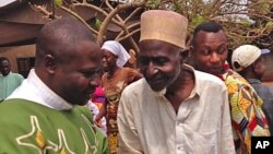 FILE - Father Justin Nary, left, greets Ousmane Mahamat, one of the 800 Muslims seeking refuge in a Catholic church in Carnot a town 200 kilometers (125 miles) from the Cameroonian border in Central African Republic, Feb. 23, 2014.