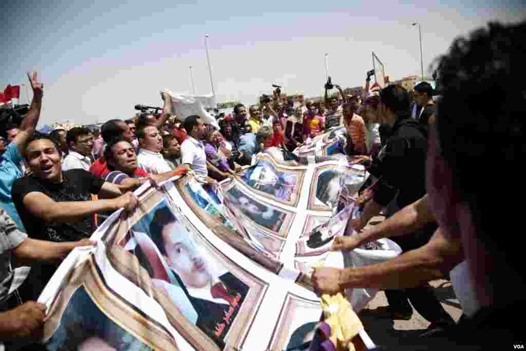 The crowd displays a banner with photos of those killed in the uprising in Cairo, June 2, 2012. (VOA/Y. Weeks)